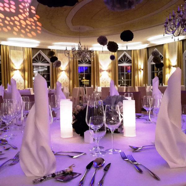 Gedeckte Tische in Festsaal bei festlicher Beleuchtung