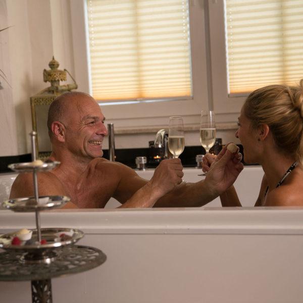 Paar mit Sektgläsern in einer Badewanne