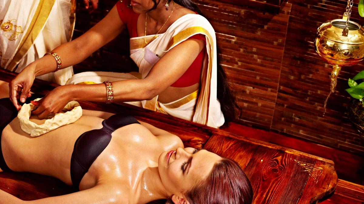 Frau in traditionellem Gewand führt eine ayurvedische Behandlung an eine Frau durch