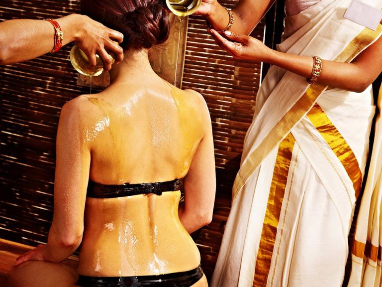 Frau bei ayurvedischer Anwendung mit Ölgüssen