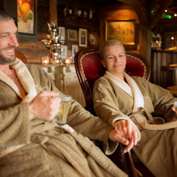 Paar in Bademänteln mit Teegläsern