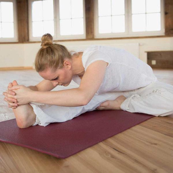Frau auf einer Yogamatte bei der Dehnung